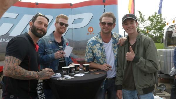 Moderatoren Jens Kuck, Nils Egtermeyer und Det Müller mit einem Fan.