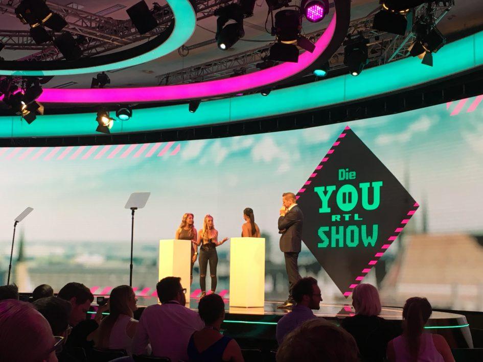 """Christian Nienaber, Bereichsleiter Digital, mit (RTL II News-)Moderatorin Steffi Brungs, Roxi und Sophia von der Mjunik-WG (von rechts) während der RTLII YOU-Show in der """"Motion Hall"""""""